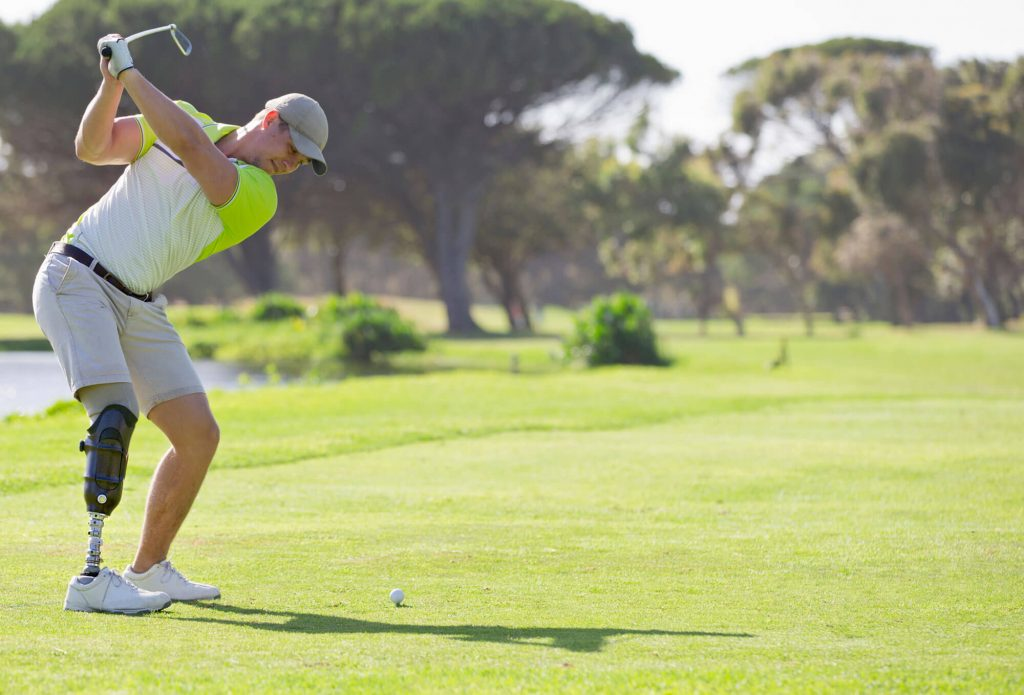 Golfer with prosthetic leg taking a swing