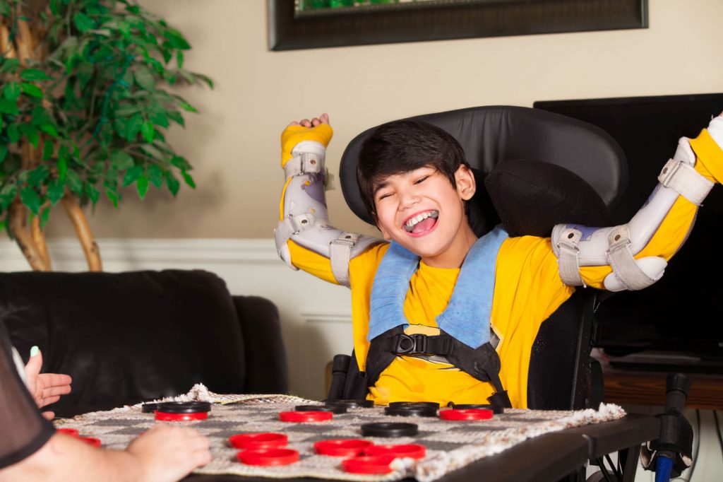 Boy cheering with arm braces on